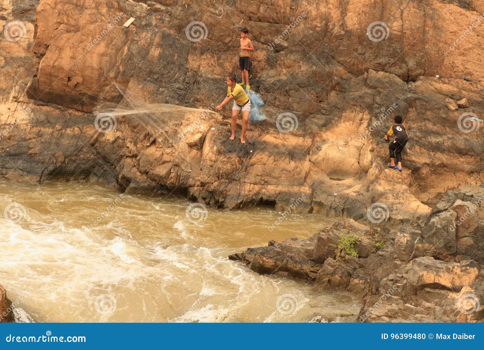 Mensen die met een rudimentair netwerk in de Mekong rivier bij Don Khon-eiland op Laos vissen