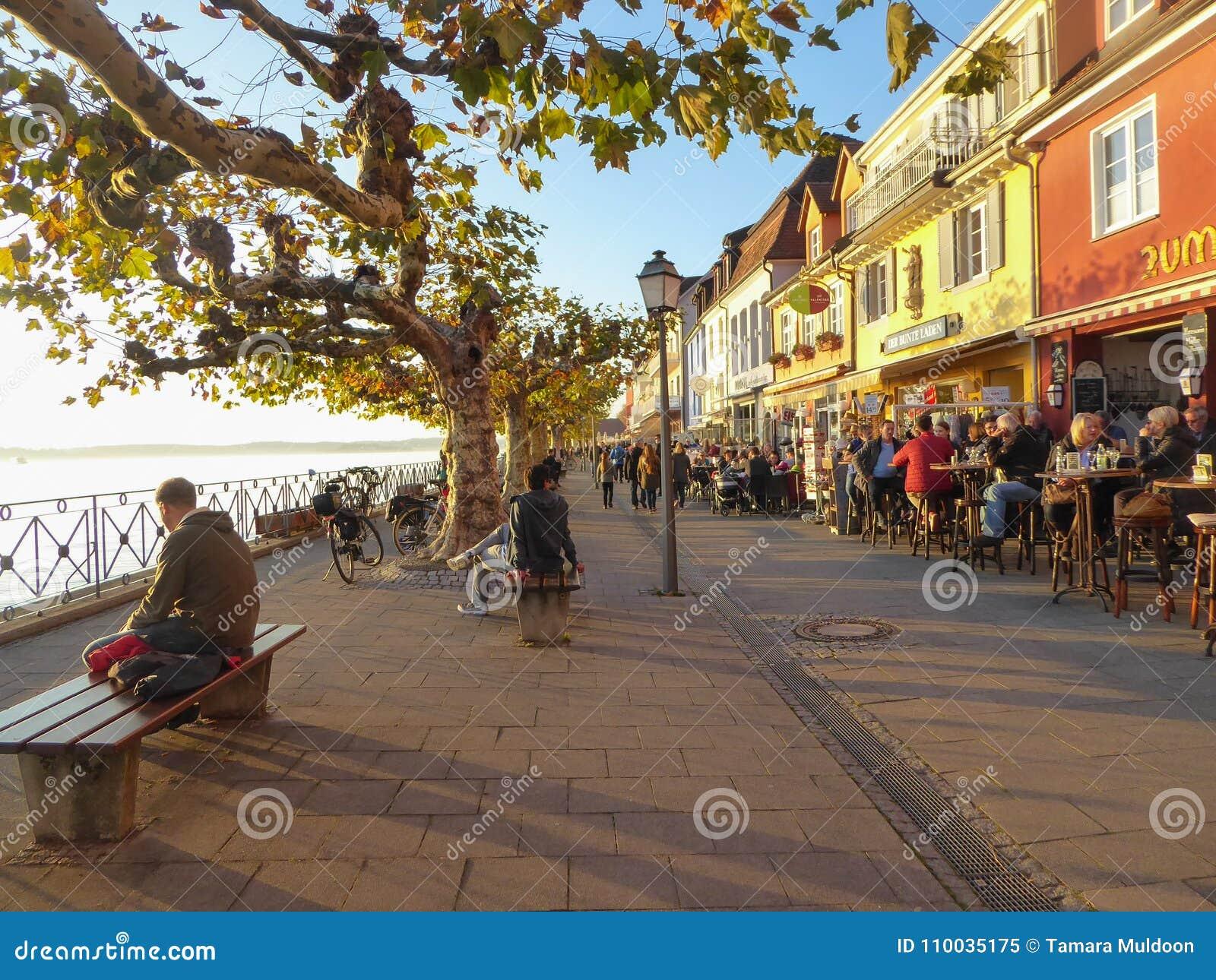 Mensen die middag van zon op kustpromenade genieten in Meersburg Duitsland