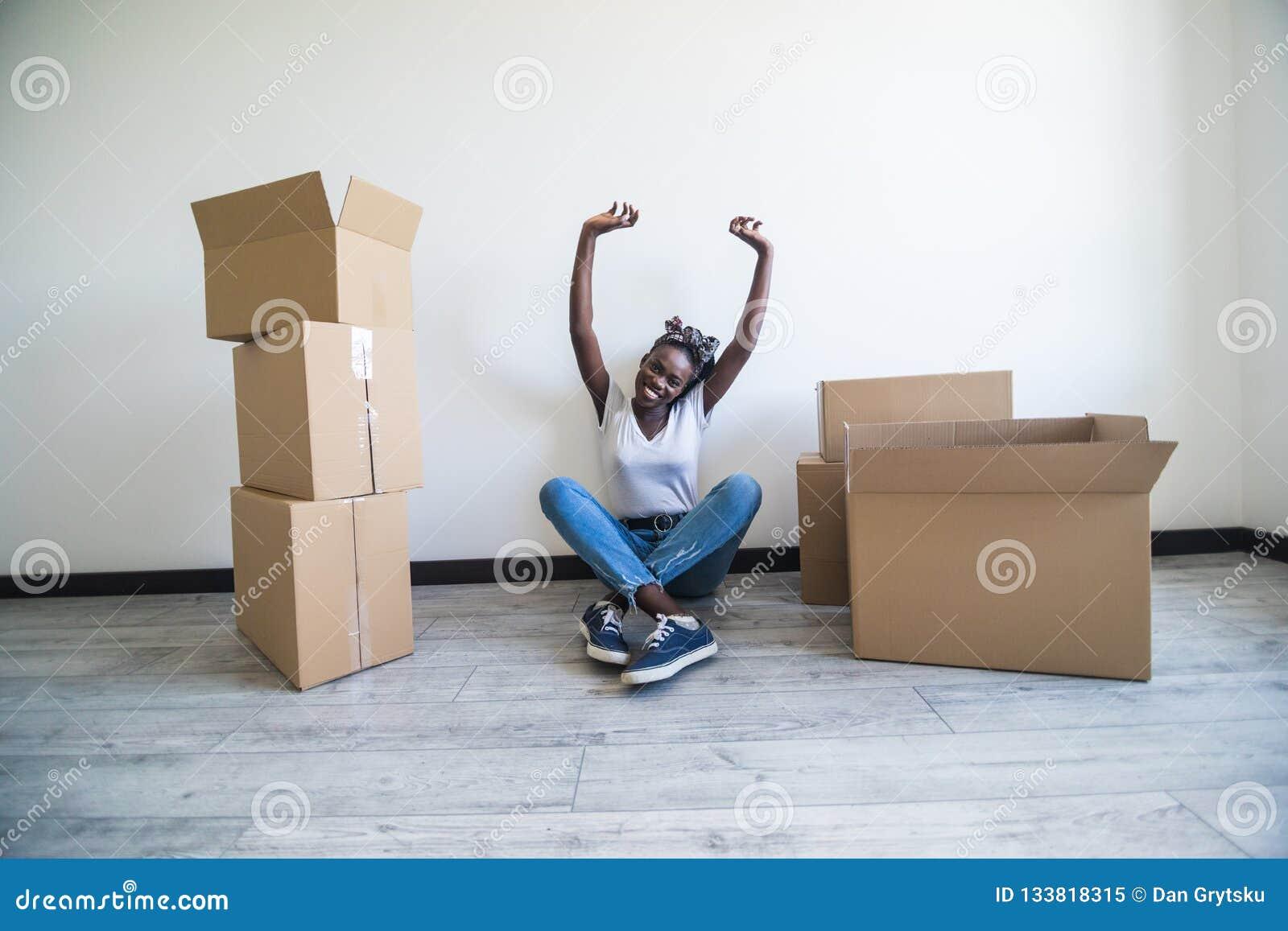 Mensen die, die nieuw plaats en reparatieconcept bewegen - gelukkige Afrikaanse Amerikaanse jonge vrouwenzitting in nieuwe flat e