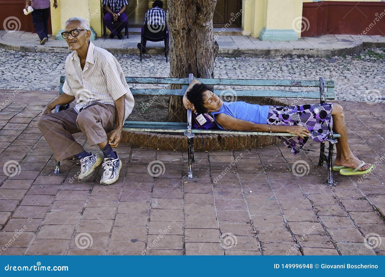 Mensen die op een bank in Trinidad DE Cuba rusten