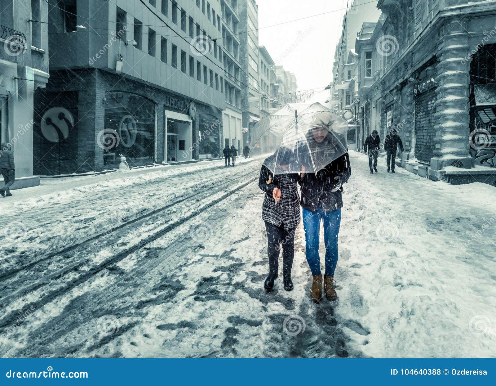 Mensen die op een sneeuwdag bij populaire Istiklal-Straat van Beyoglu lopen