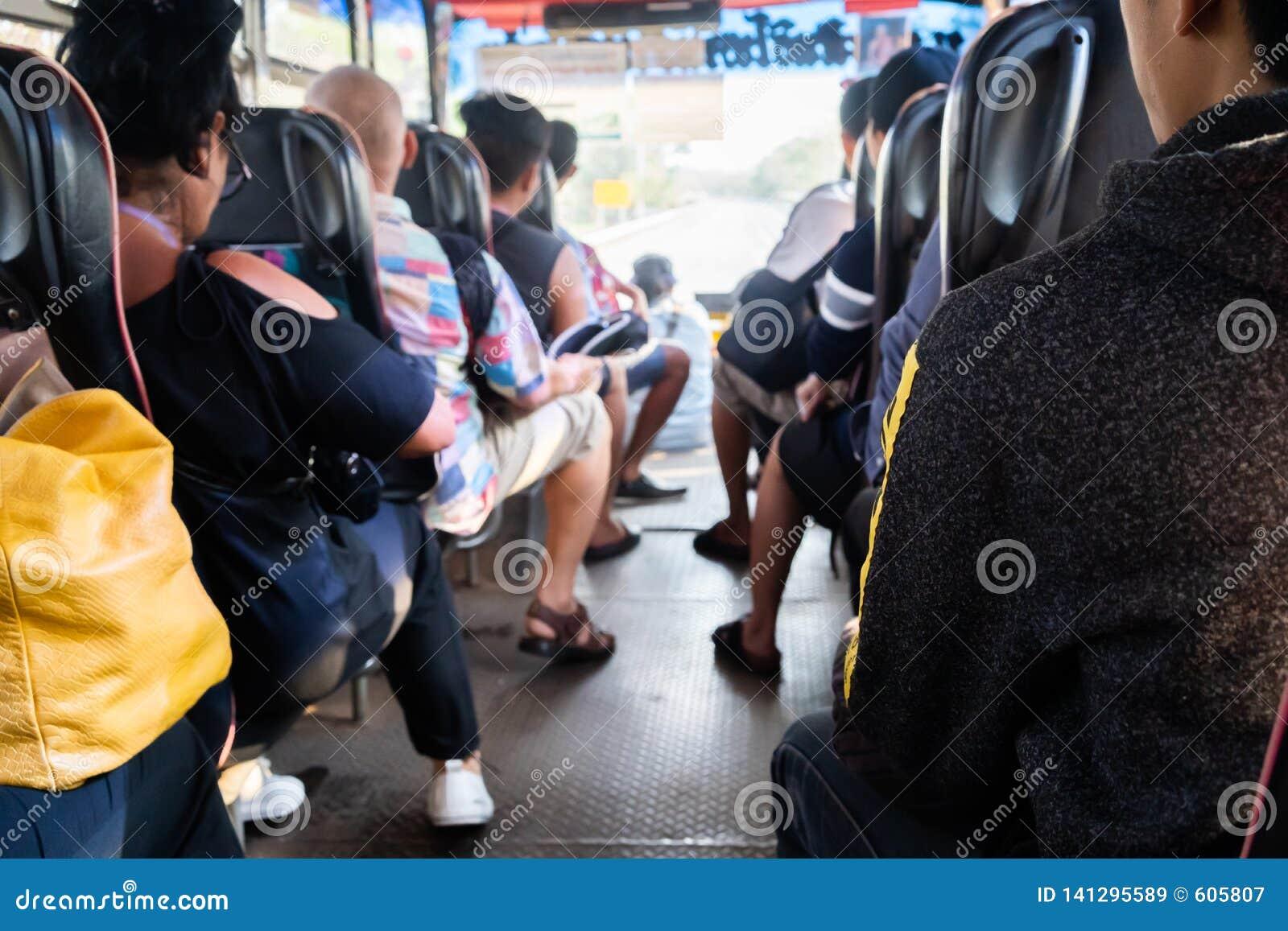Mensen die op zetel in achtermening over de bus zitten