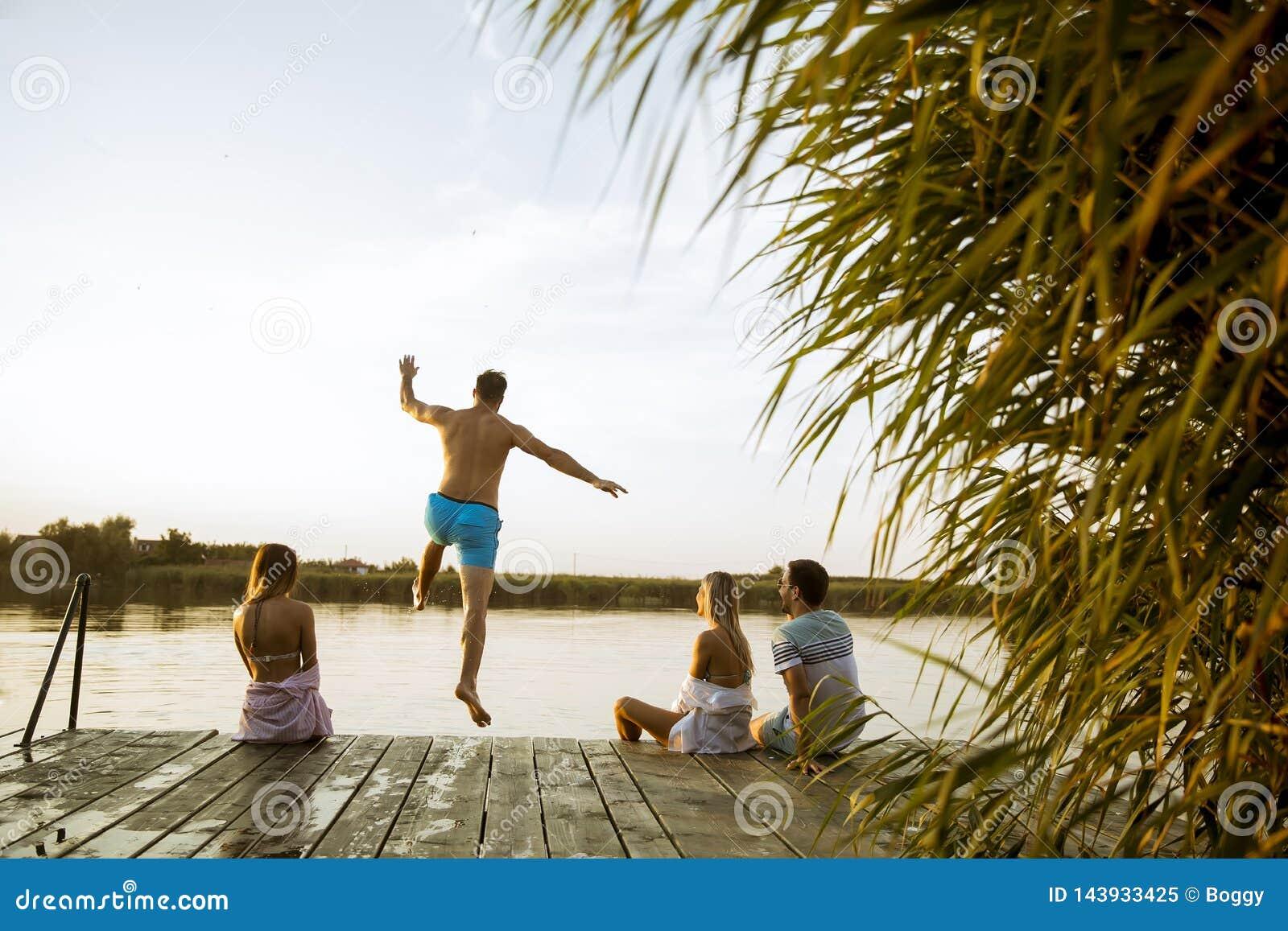 Mensen die pret hebben bij het meer op een de zomerdag
