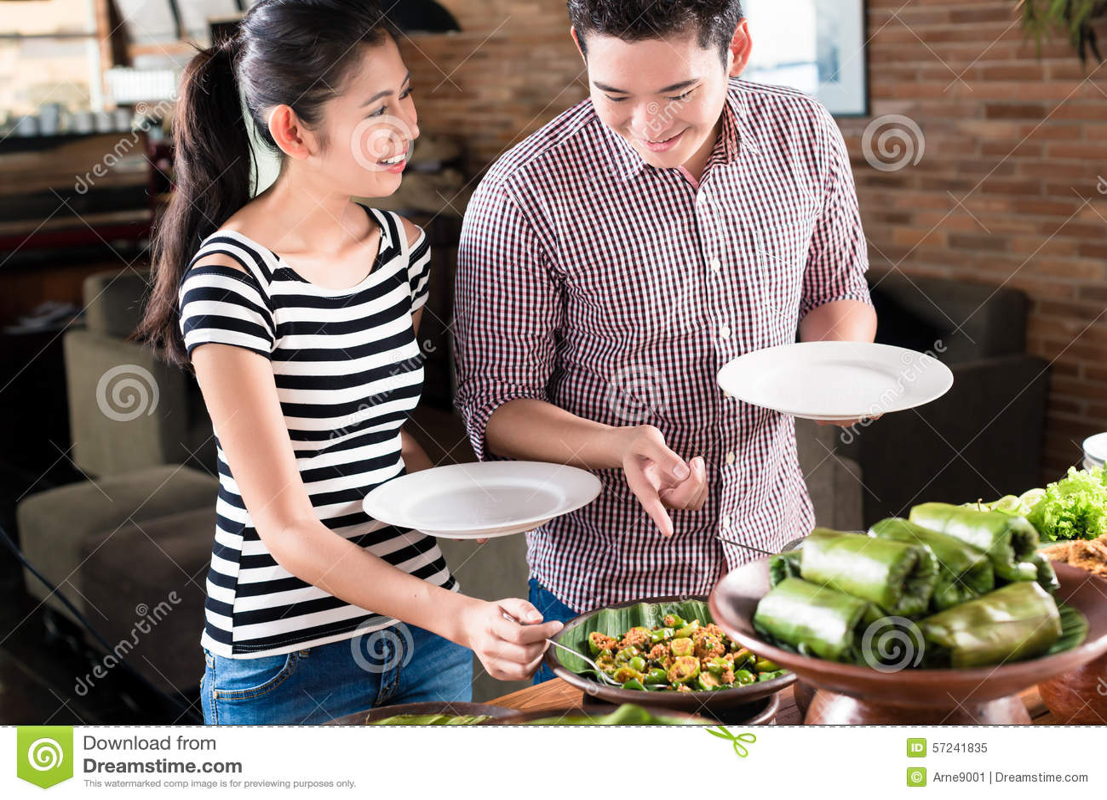 Mensen die voedsel kiezen bij Indonesisch buffet in restaurant