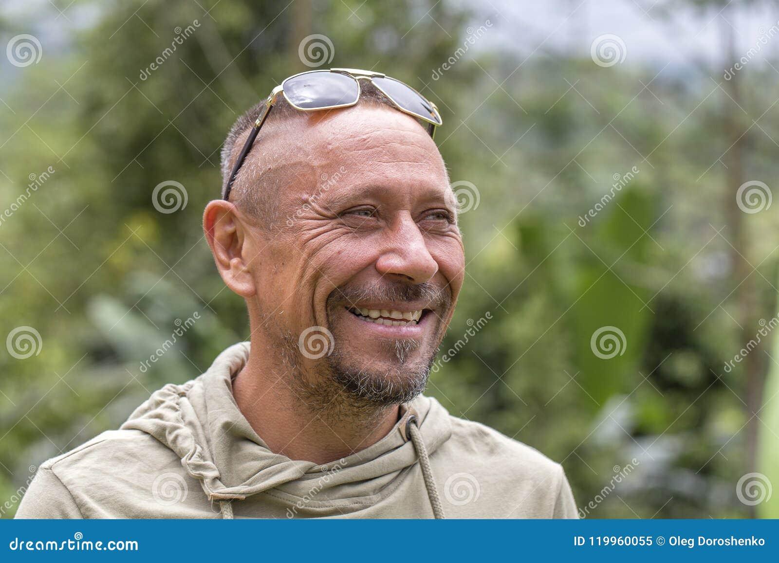 Mensen en levensstijlconcept Gelukkige ongeschoren mens op middelbare leeftijd met vrolijke glimlach openlucht tegen groene aarda