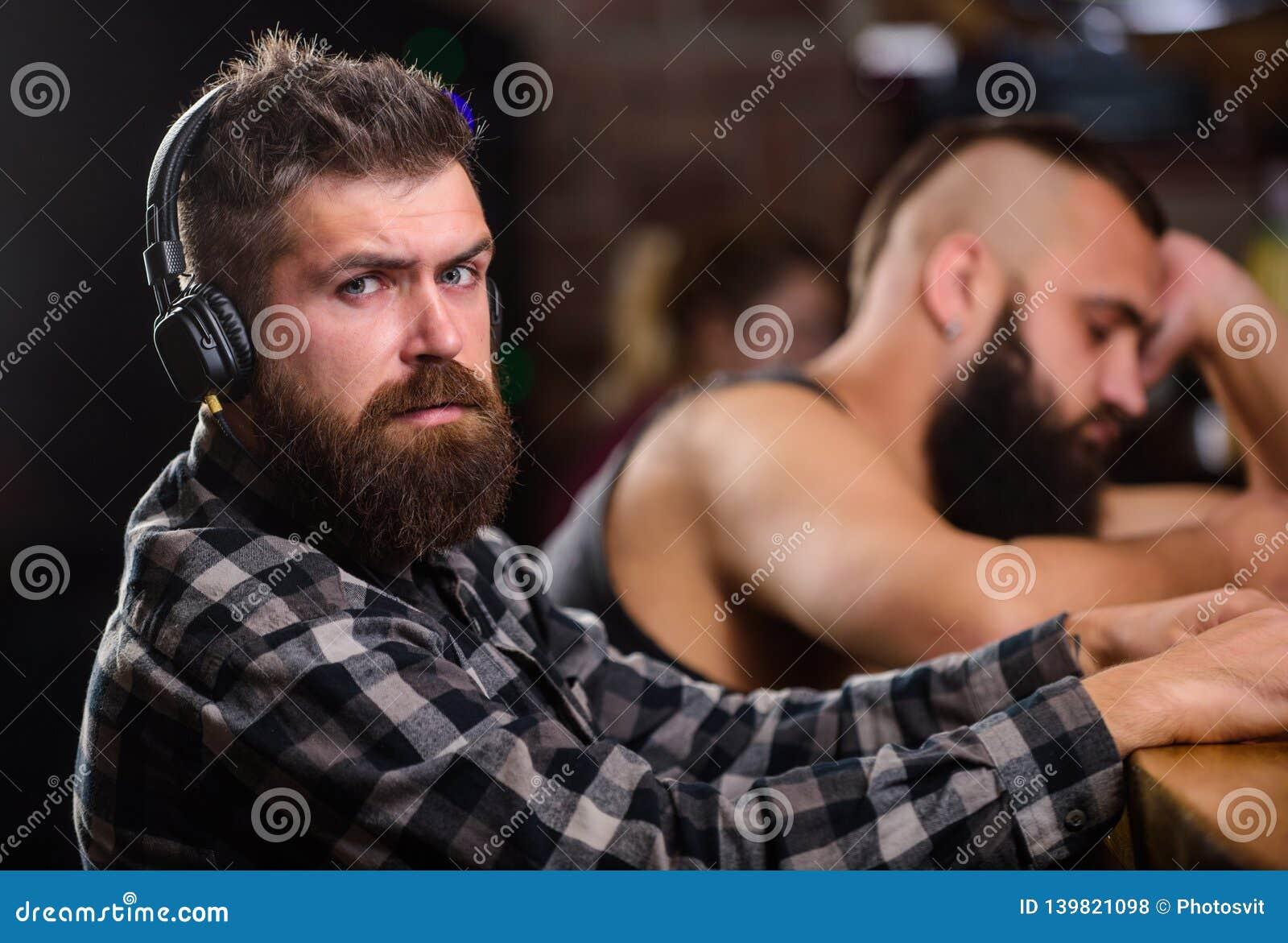 Mensen met hoofdtelefoons en smartphone het ontspannen bij bar Vermijd mededeling Vluchtwerkelijkheid Vrijdagontspanning in bar
