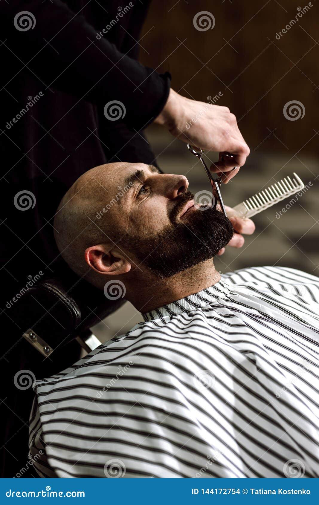 Mensen` s manier De baard van de kappersschaar van de brutale mens in de modieuze herenkapper