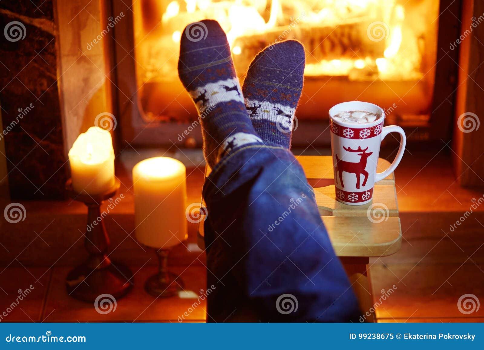 Mensen` s voeten in warme sokken met grote mok hete chocolade en murshmallows dichtbij open haard