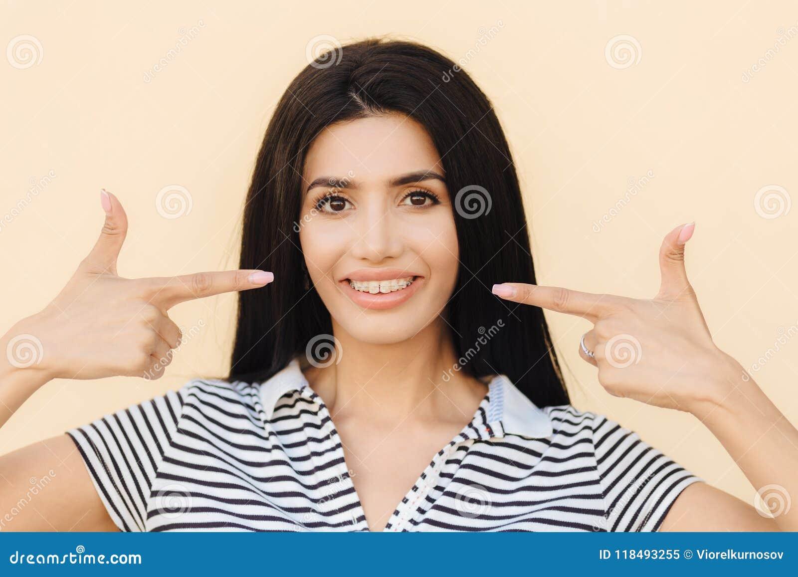 Mensen, schoonheid en reclameconcept De donkerbruine jonge vrouw met zachte glimlach, wijst op bij mond met brede glimlach, heeft