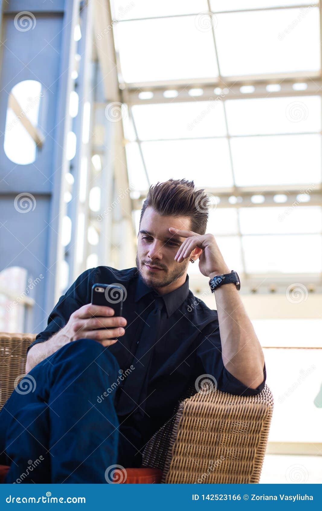 Mensen telefoneert het trotse CEO lezings bedrijfsnieuws in Internet via cel, zitting in vertrek