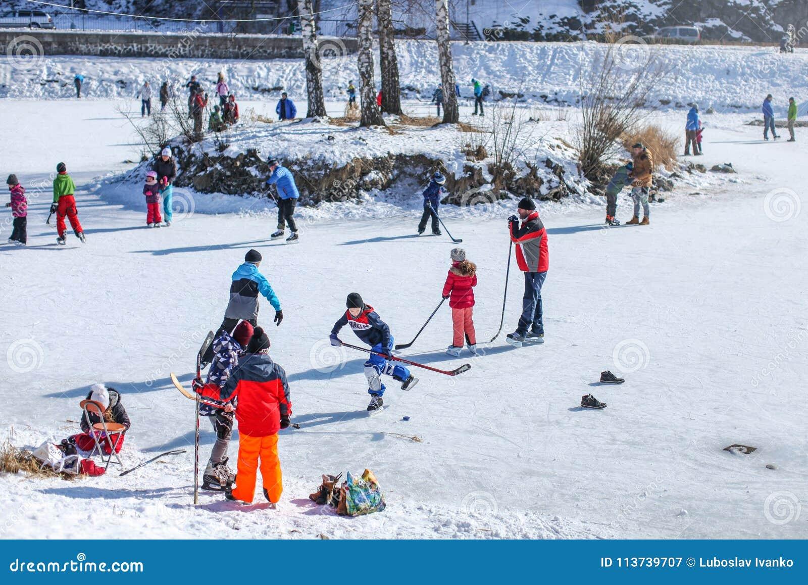 Mensen van alle leeftijdsgroepen die van zonnige dag, schaatsend en speelijshockey op een bevroren meer genieten, wanneer tempera