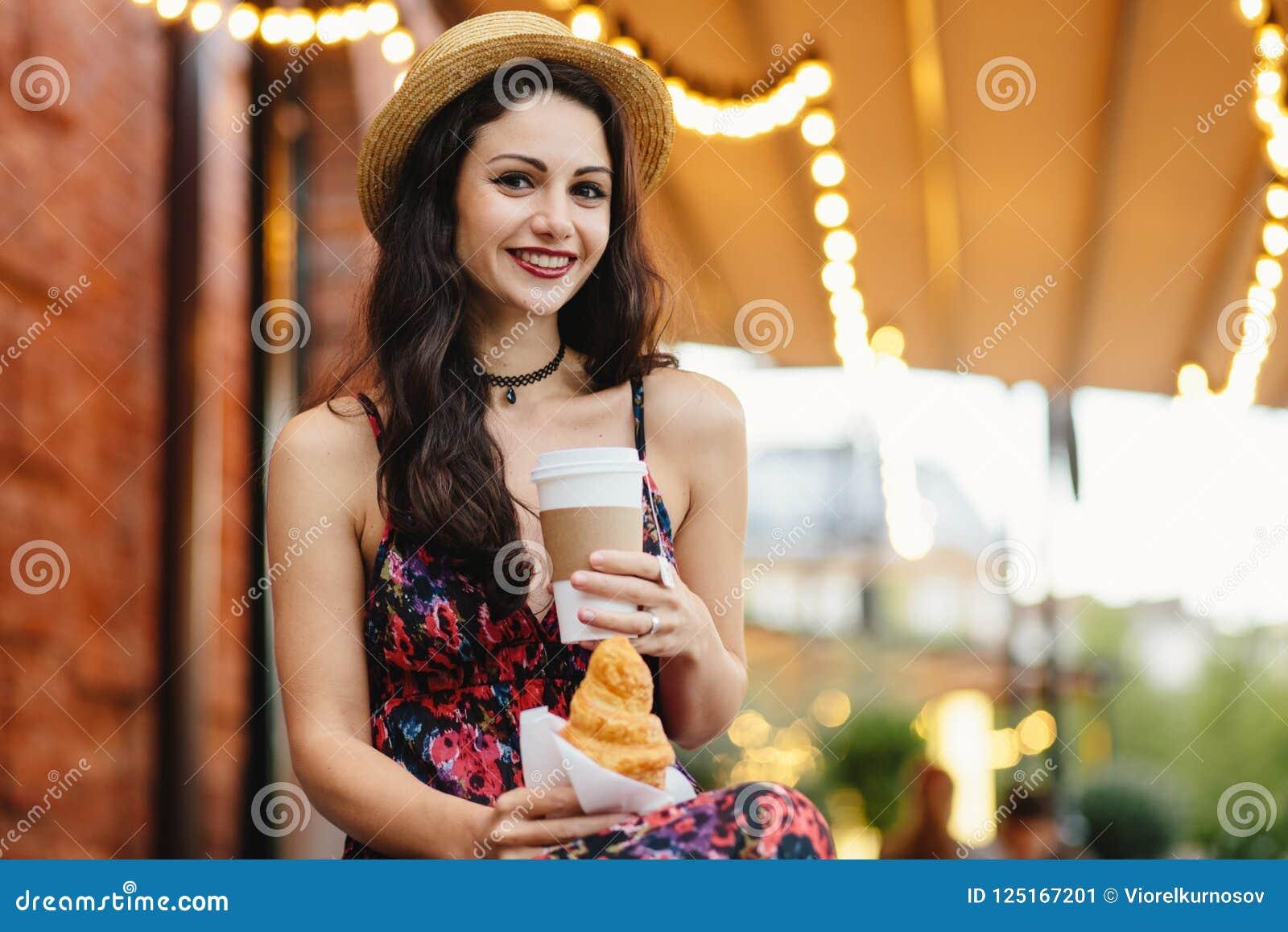 Mensen, voedsel, rust en levensstijlconcept Donkerbruine vrouw met lang haar, die de zomerkleding en hoed, het drinken meeneem ko