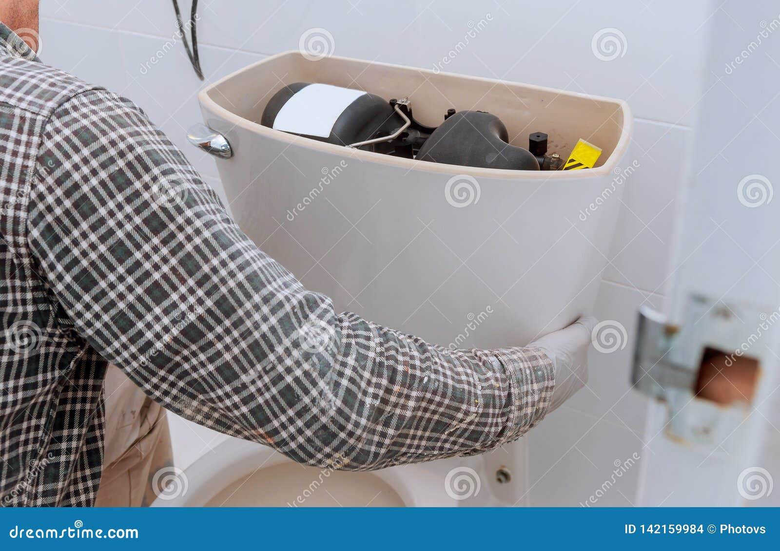 Mensenarbeider die met toilettank herstellen in badkamers, close-up
