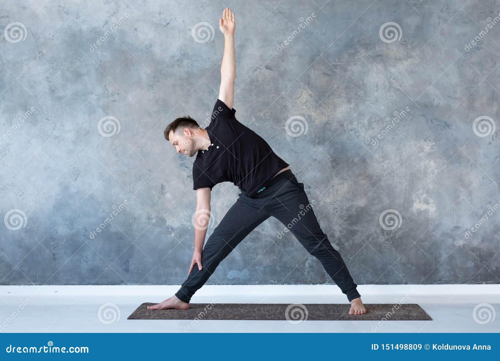 Mensenbeginner het praktizeren de yoga die trikonasana doet stelt