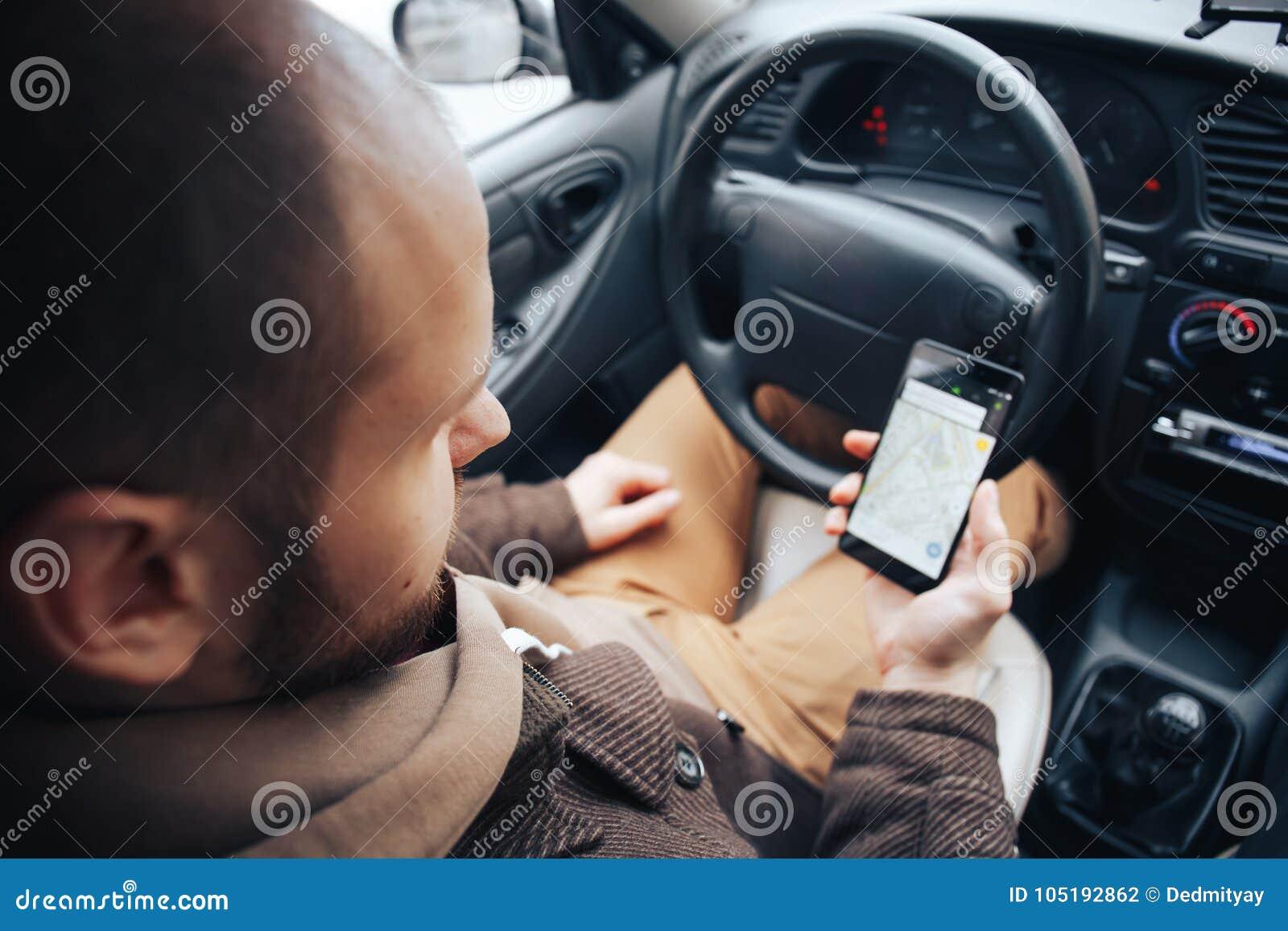 Mensenbestuurder die mobiele telefoon met gps toepassing in zijn auto, moderne navigatietechnologie voor reis houden en concept d