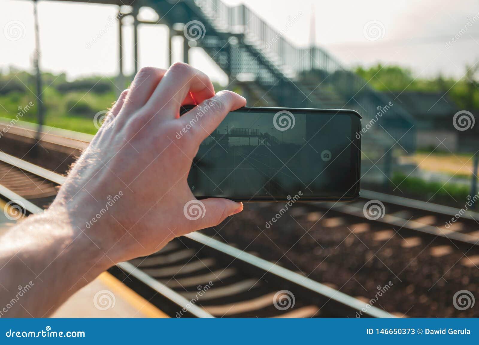 Mensenhand die een smartphone houden en een foto van station nemen tijdens de lente, middag