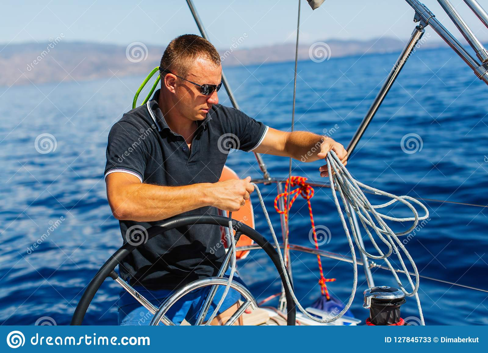 Mensenkapitein bij de roercontroles van een varend jacht Sport