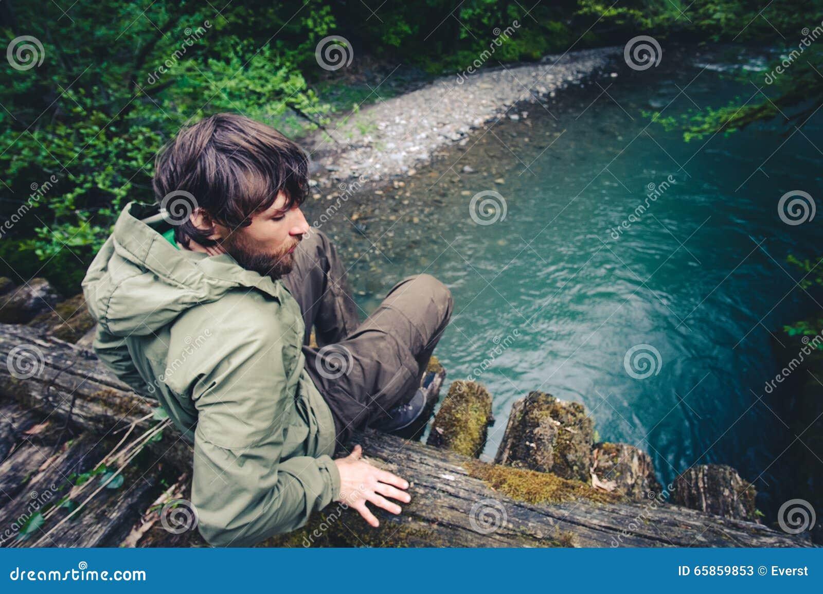 Mensenreiziger het ontspannen op houten brug over rivier