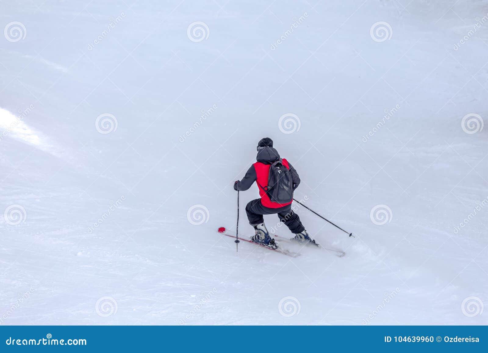 Download Mensenskiër Met Rode Laag En Het Zwarte Rugzak Ski?en Stock Foto - Afbeelding bestaande uit bovenkant, exemplaar: 104639960