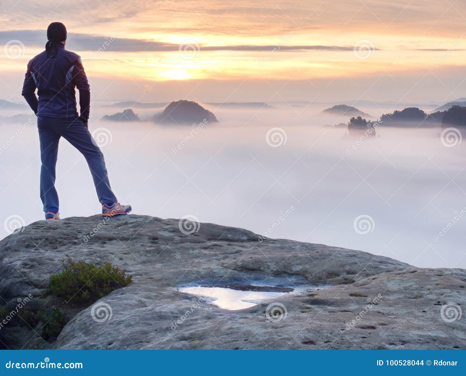 Mensentribunes alleen op de piek van rots Wandelaar het letten op aan de herfstzon bij horizon