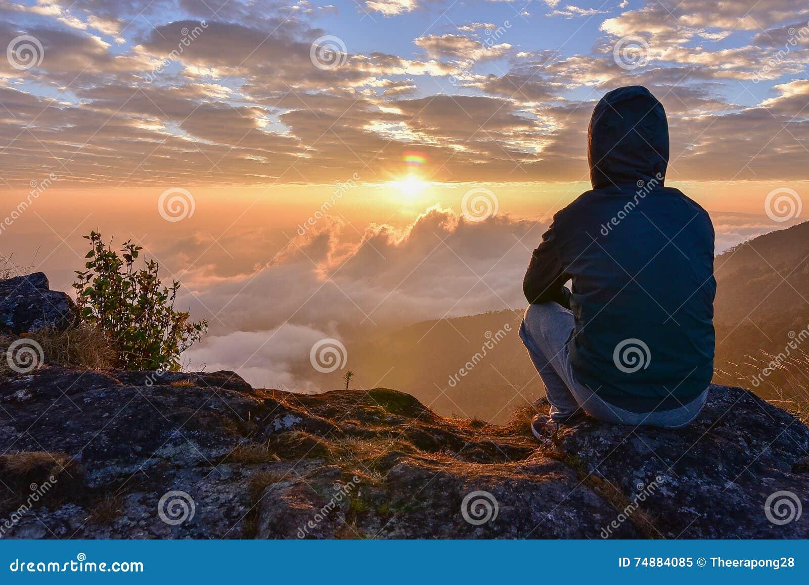 Mensenzitting op een berg voor het letten van Zonsopgang op meningen