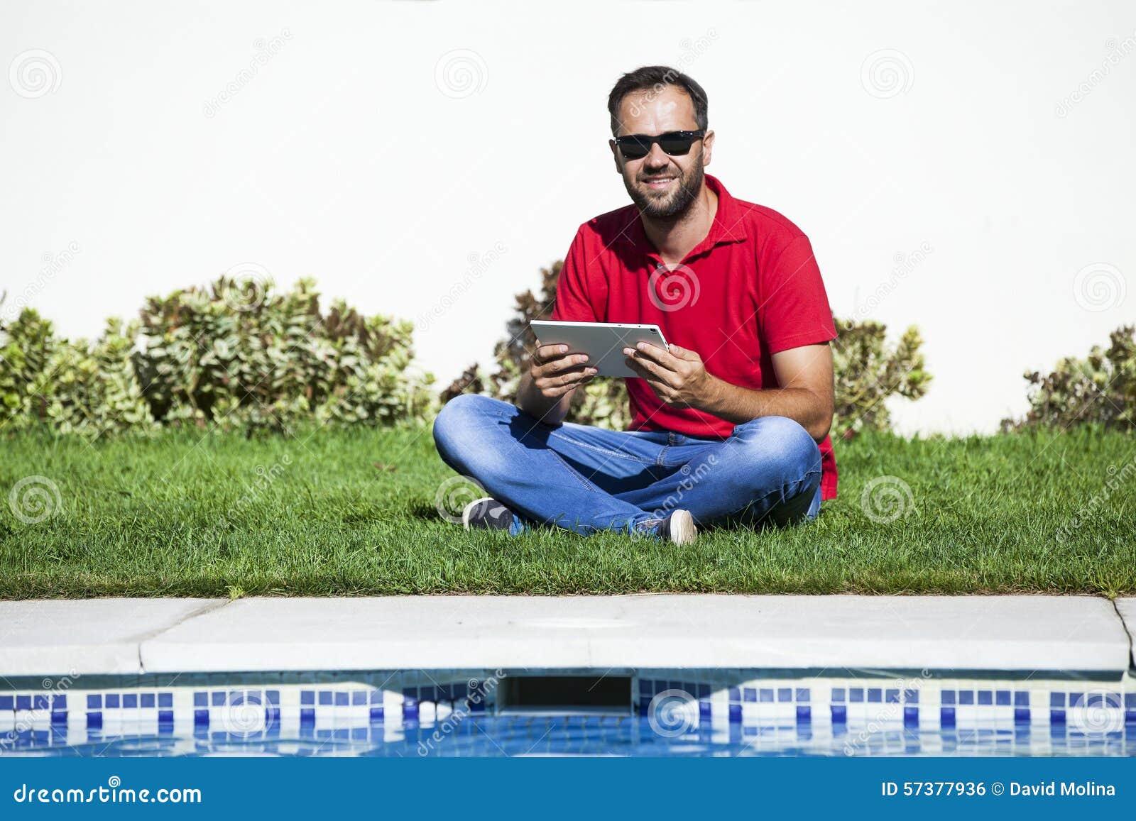 Mensenzitting op het gras, die een tablet gebruiken