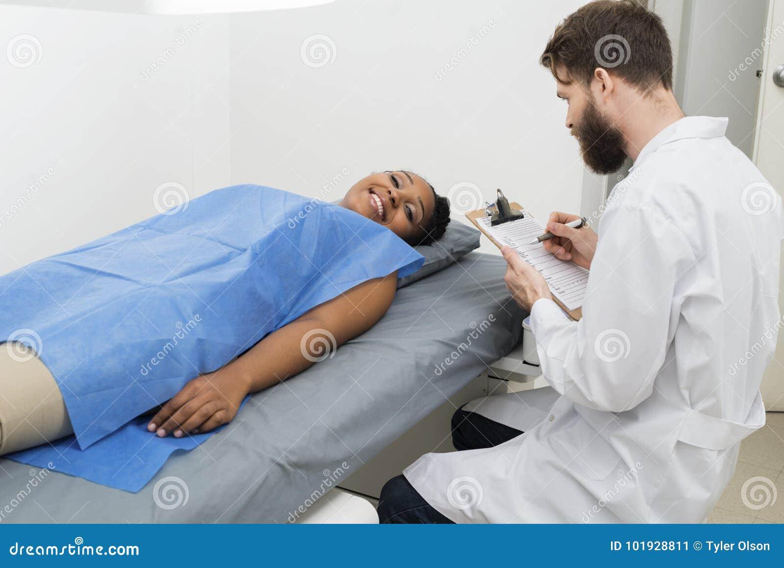 Mensonge patient femelle sur le lit tandis que docteur Holding Clipboard