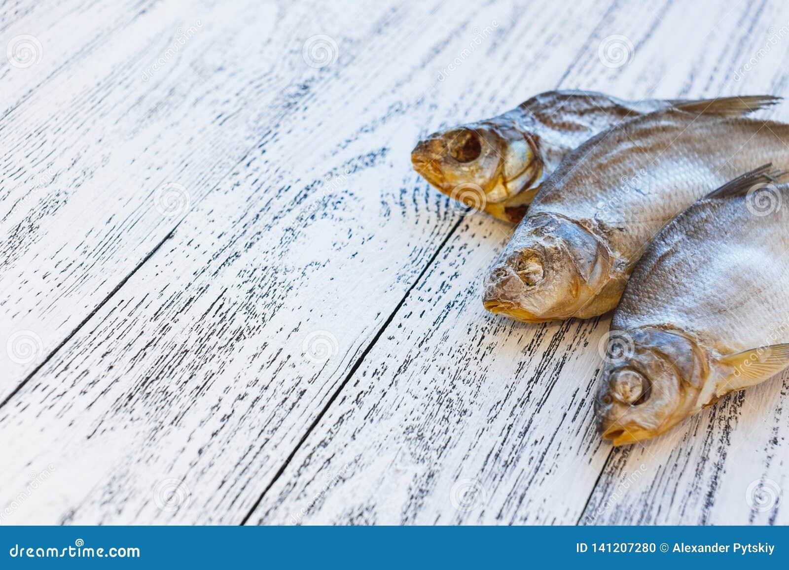 Mensonge sec de brème de trois poissons sur une table en bois légère