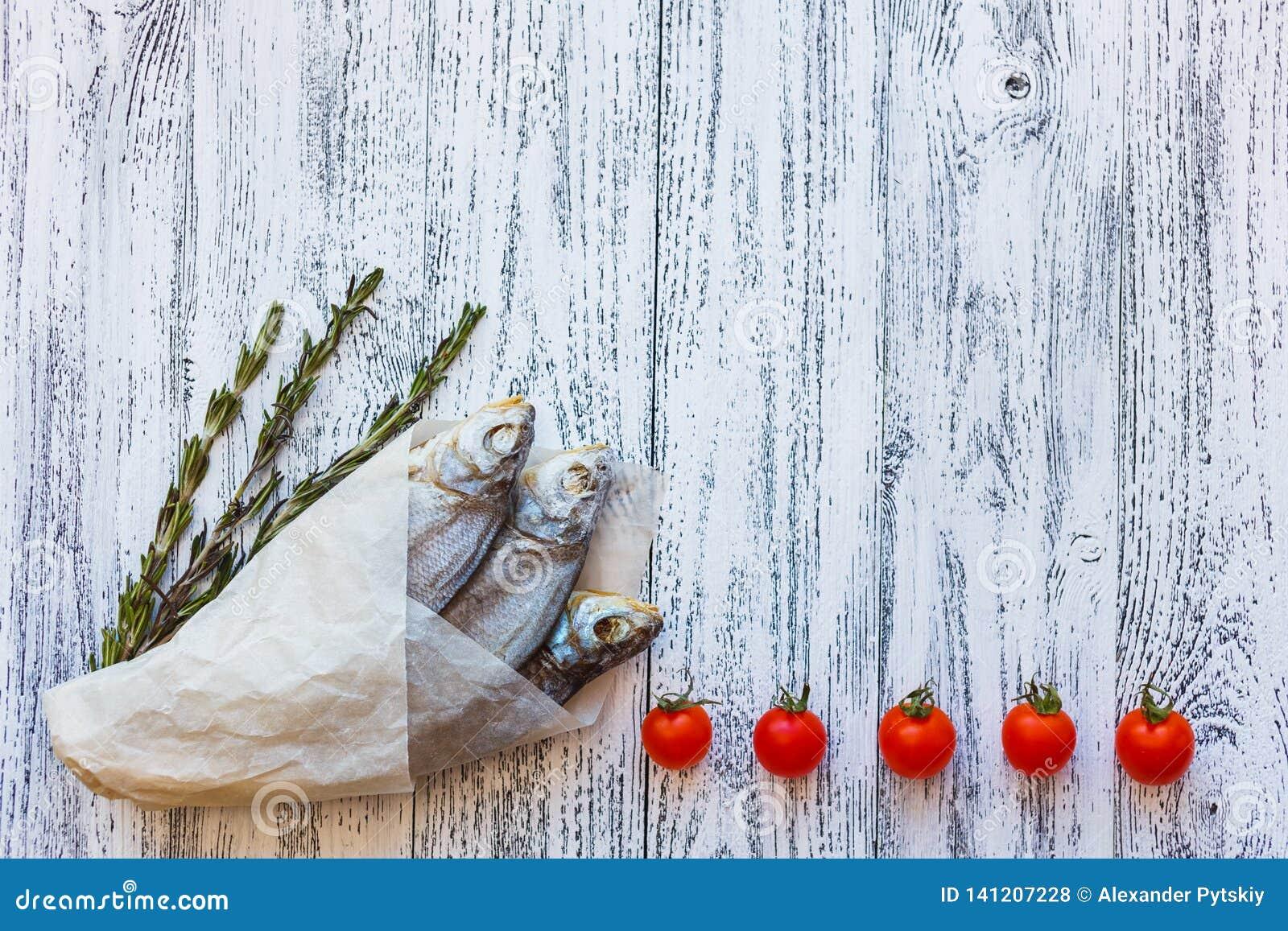 Mensonge sec de brème de trois poissons sur une table en bois lumineuse dans en bas à gauche le faisant le coin