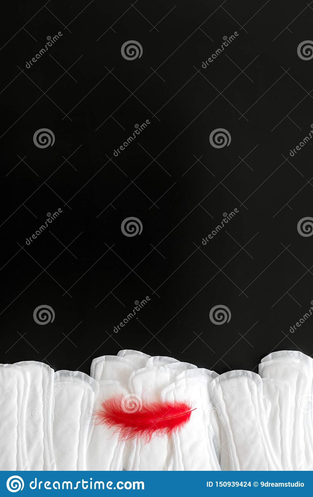Menstrual period concept with sanitary pads and red feather on black background top view mock-up