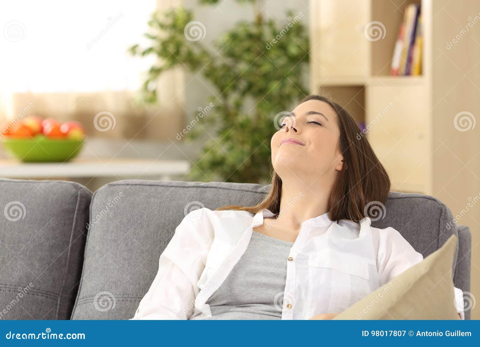 Mentira de relajación satisfecha de la mujer en un sofá en casa