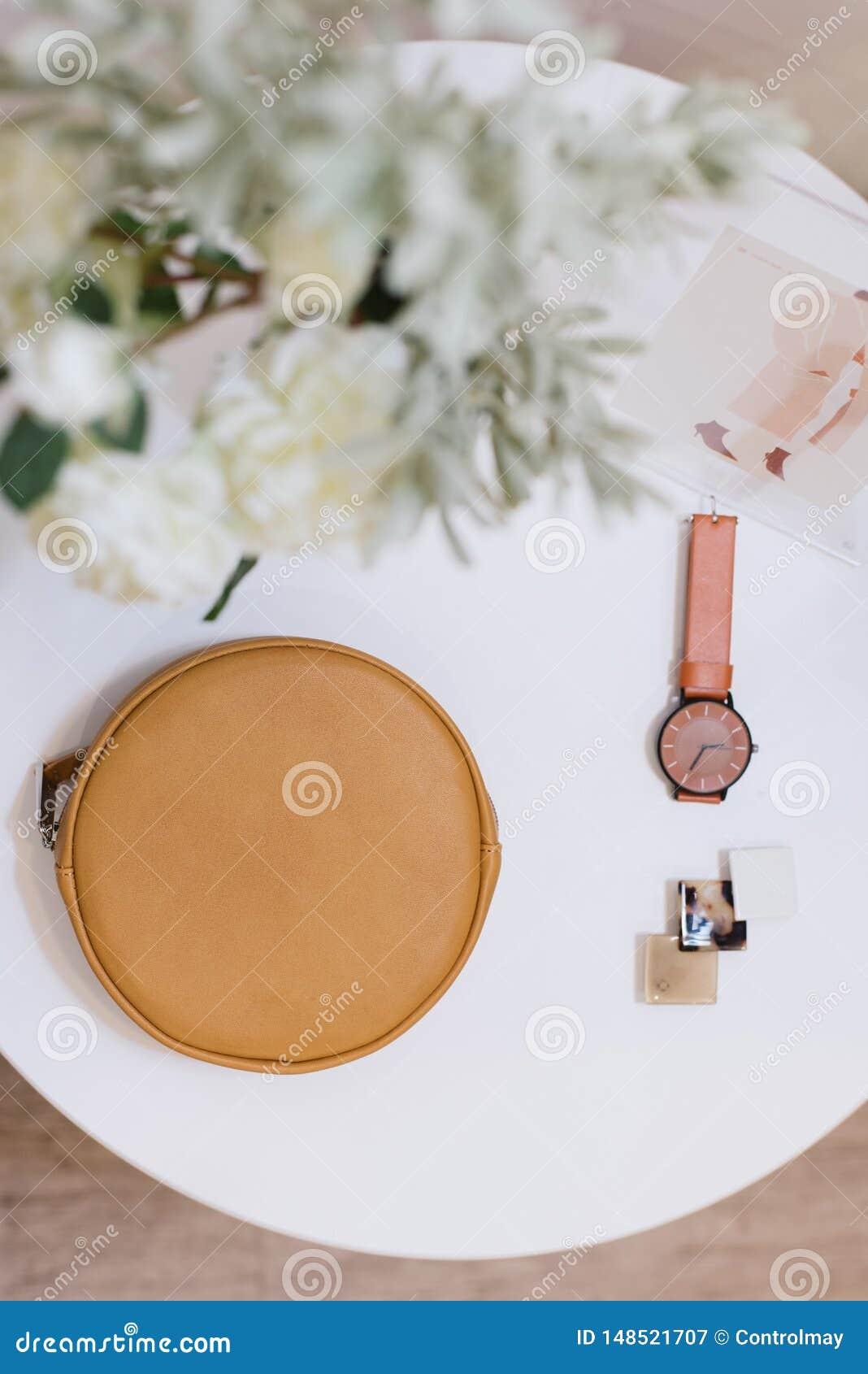 Mentira do saco, do relógio e do prendedor de cabelo em uma tabela branca
