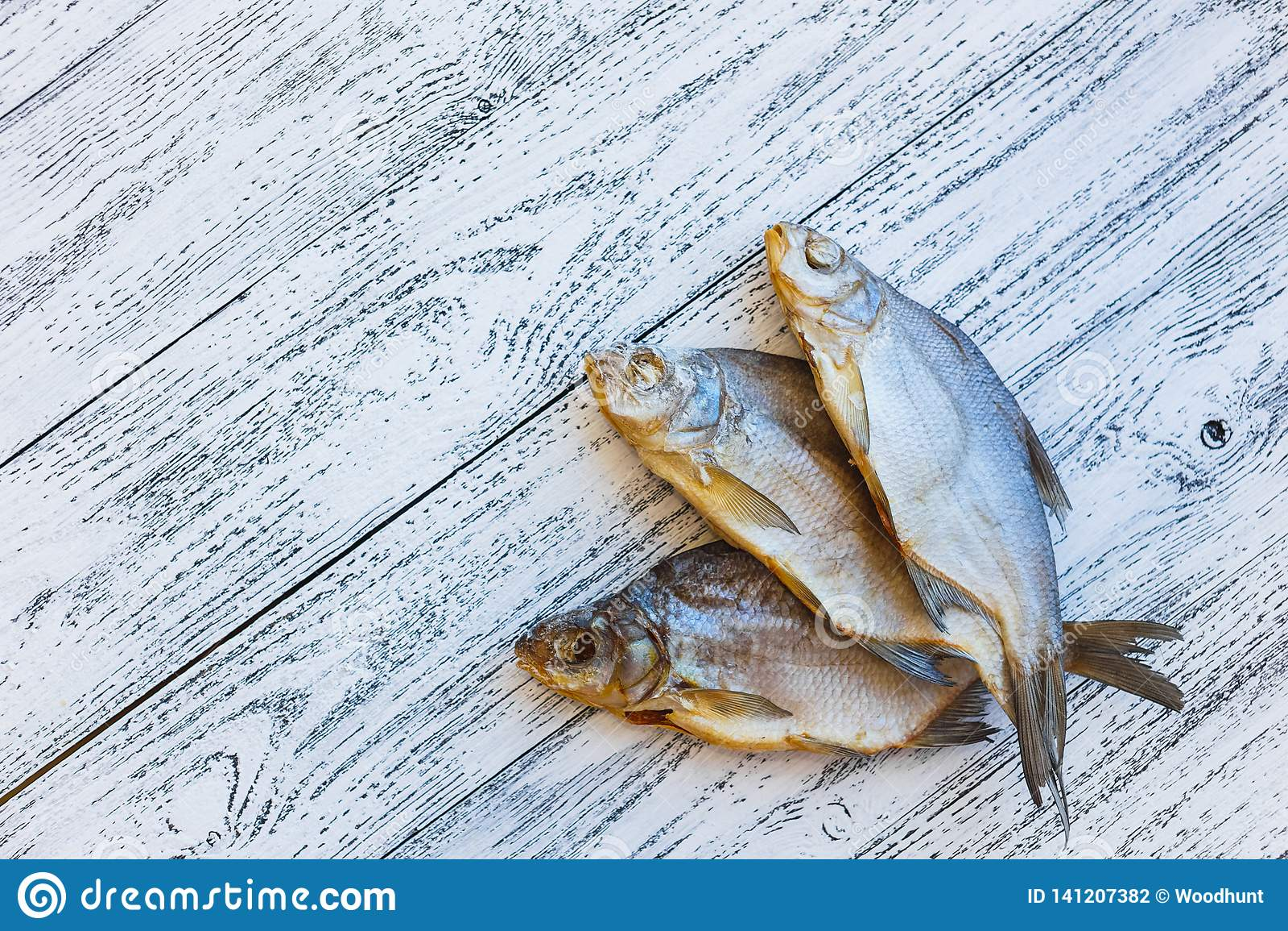Mentira secada de la brema de tres pescados en una tabla de madera ligera