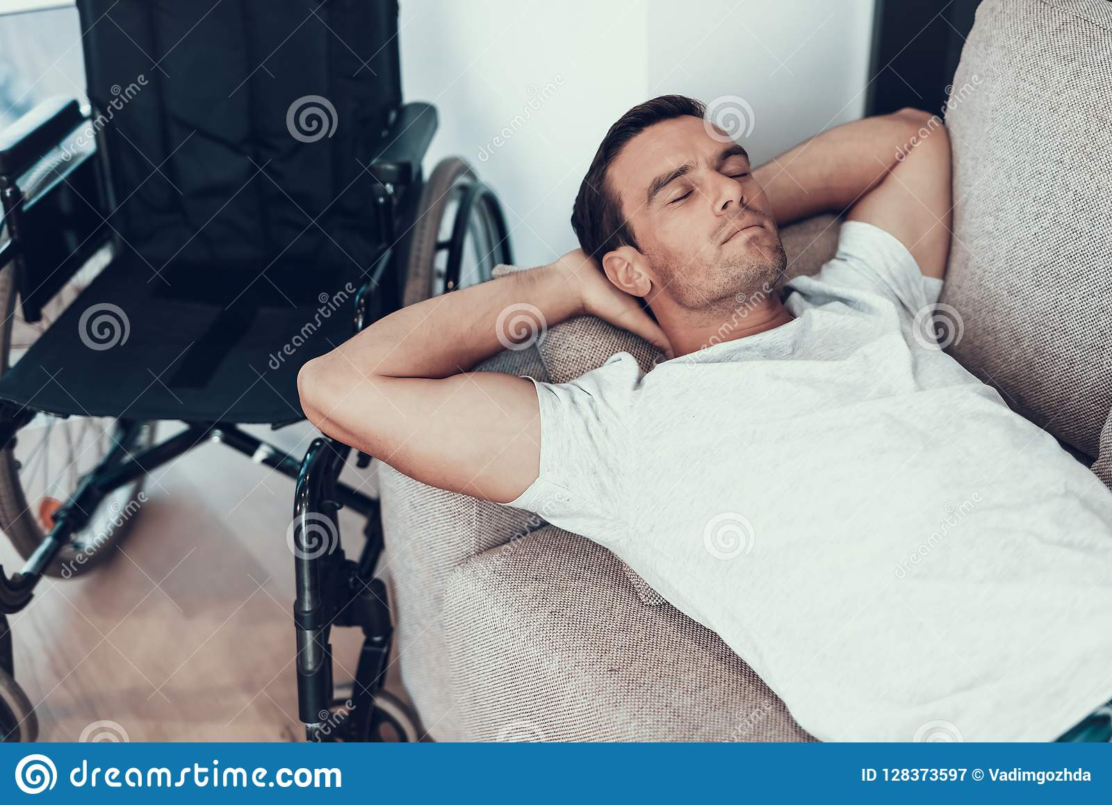 Mentiras do homem perto da cadeira de rodas em Sofa With Closed Eyes