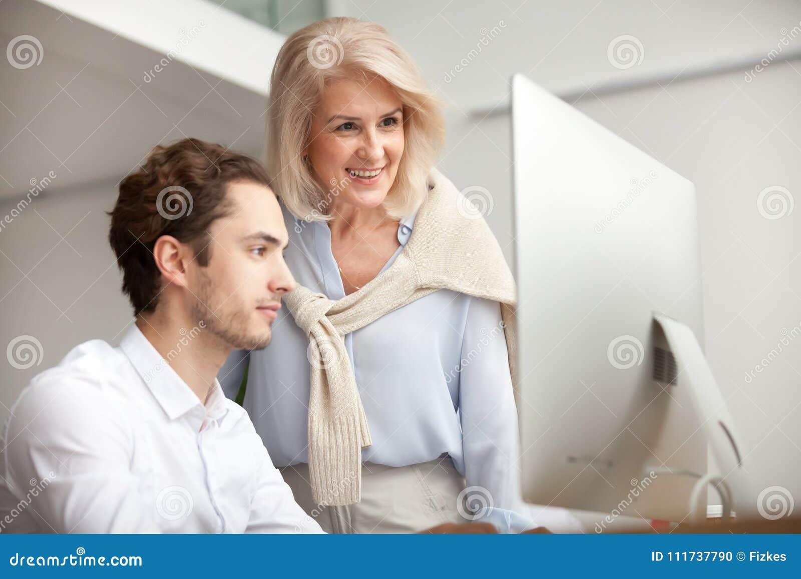 Mentor fêmea envelhecido de sorriso que olha o tela de computador que ajuda dentro