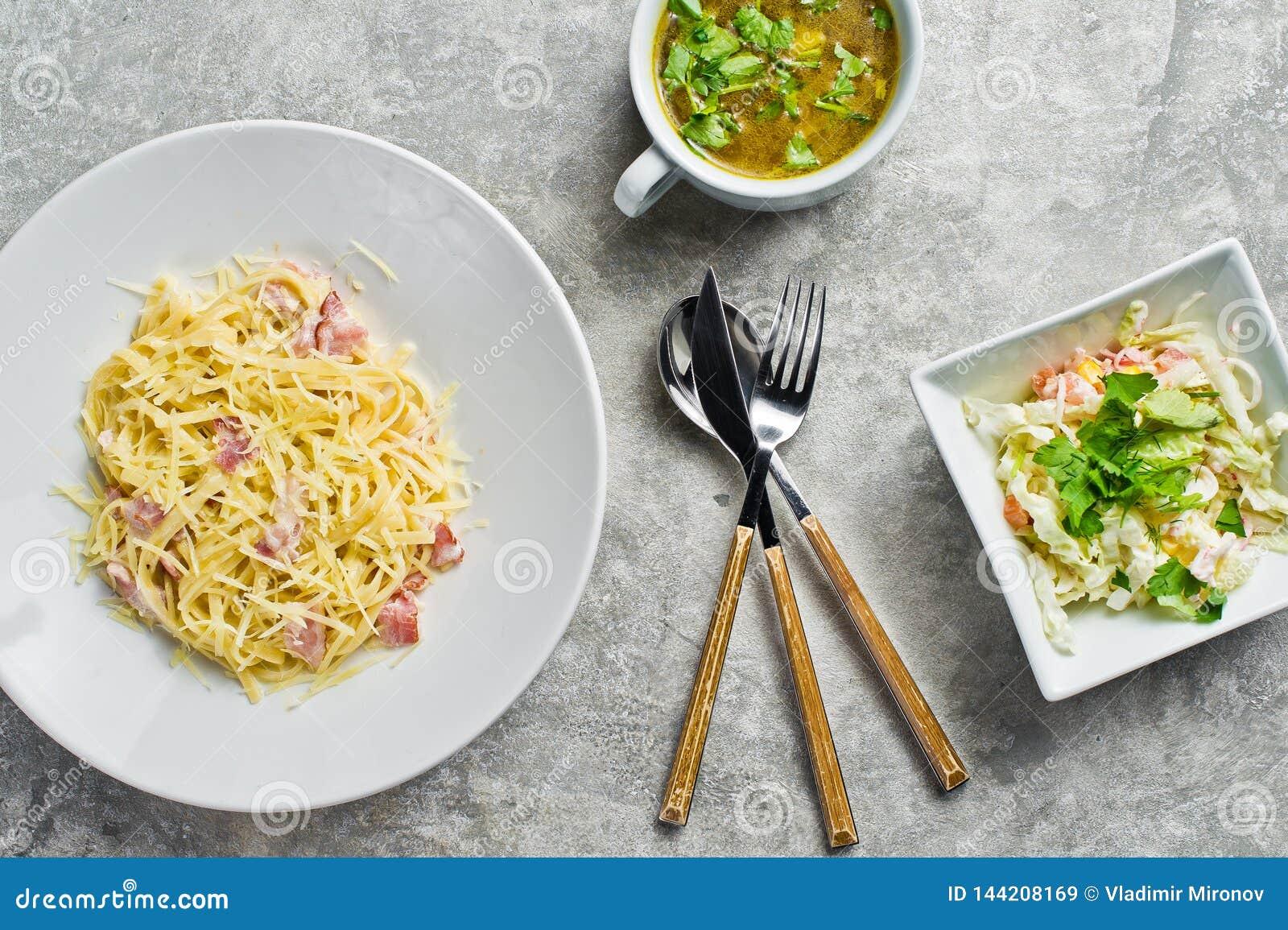 Menu del pranzo di lavoro, pasta Carbonara, insalata verde e minestra di pollo