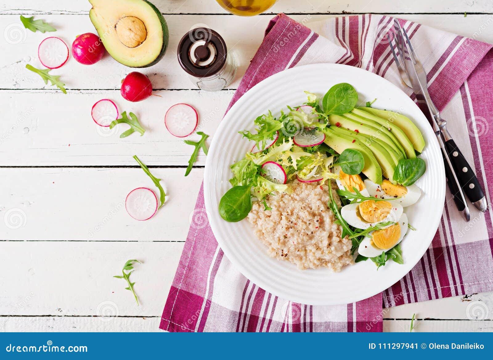 Menu dietético do café da manhã saudável Papa de aveia da farinha de aveia e salada e ovos do abacate