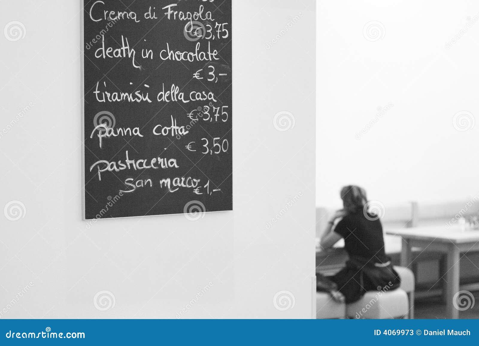 Menu em um café na parede com as mulheres que sentam-se em a
