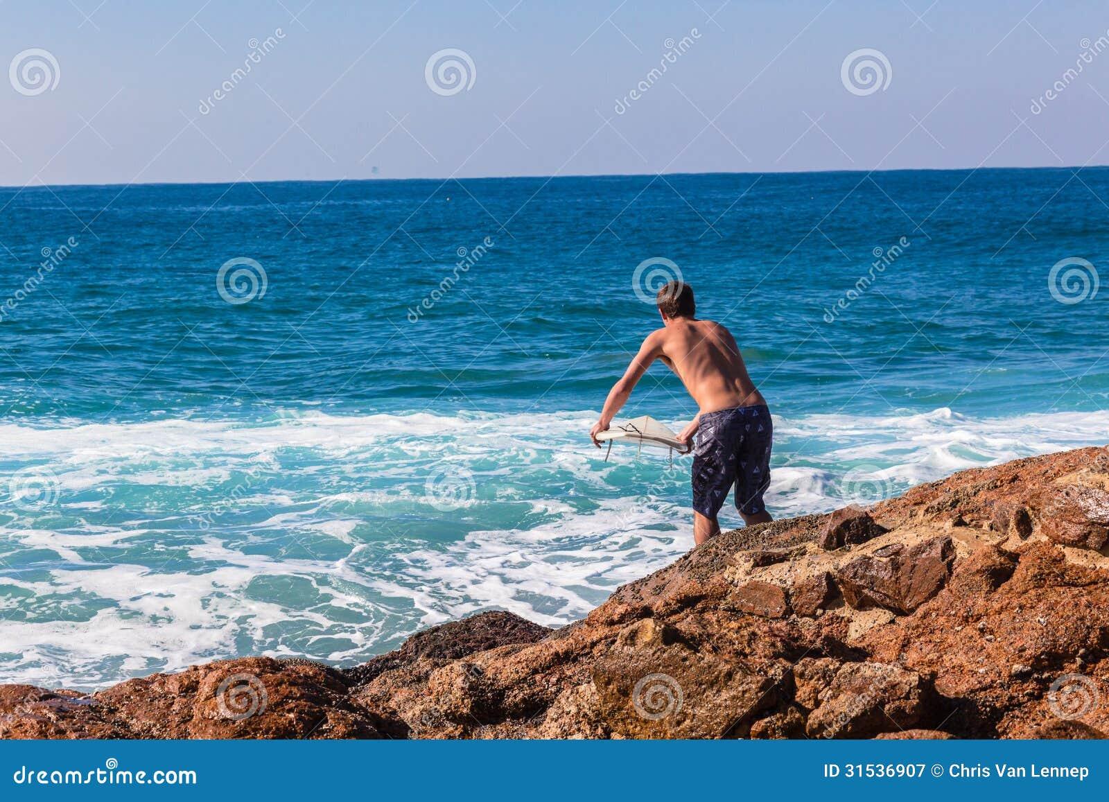 Mer d entrée de saut de roche de surfer