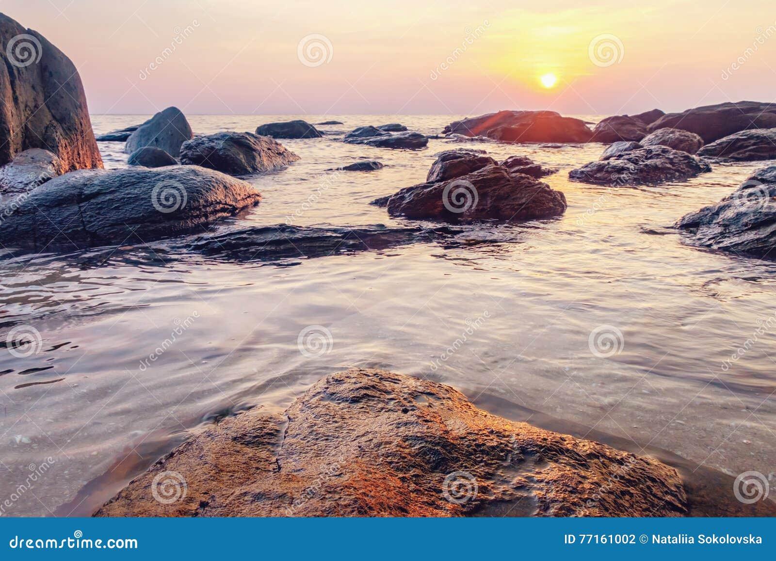 Mer foncée de nuit avec les pierres saillantes
