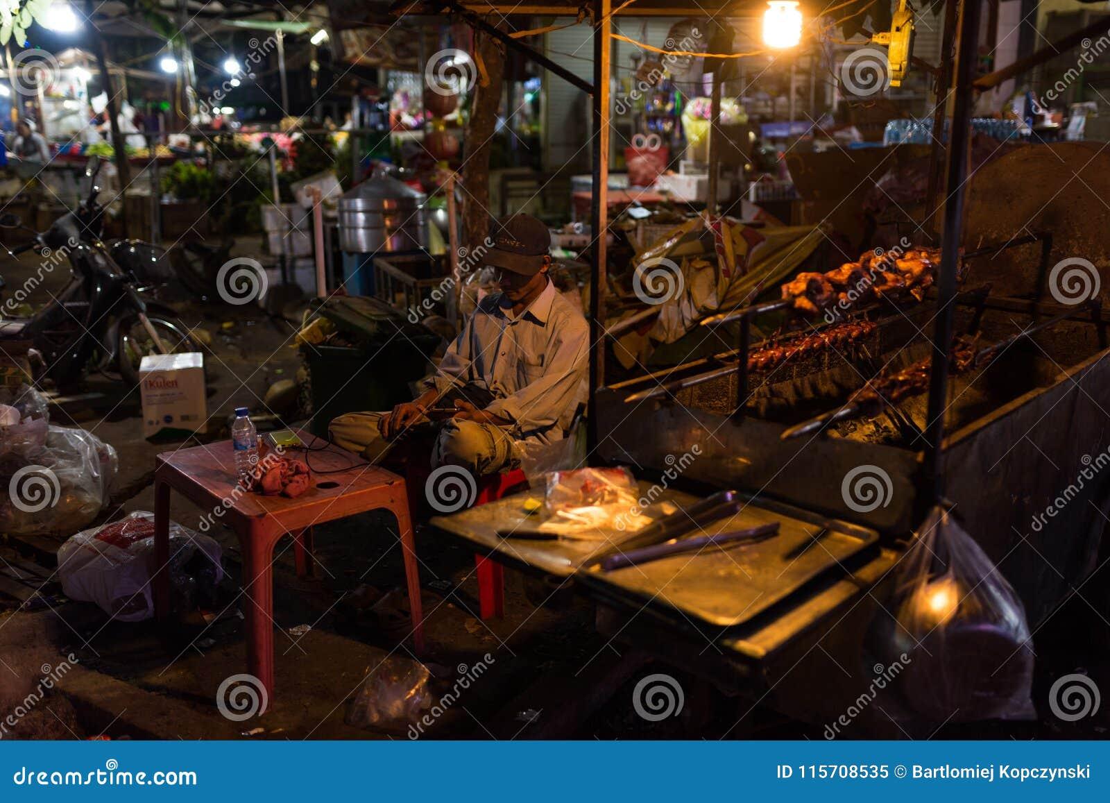 Mercado de la noche y gente del Khmer que vende la comida