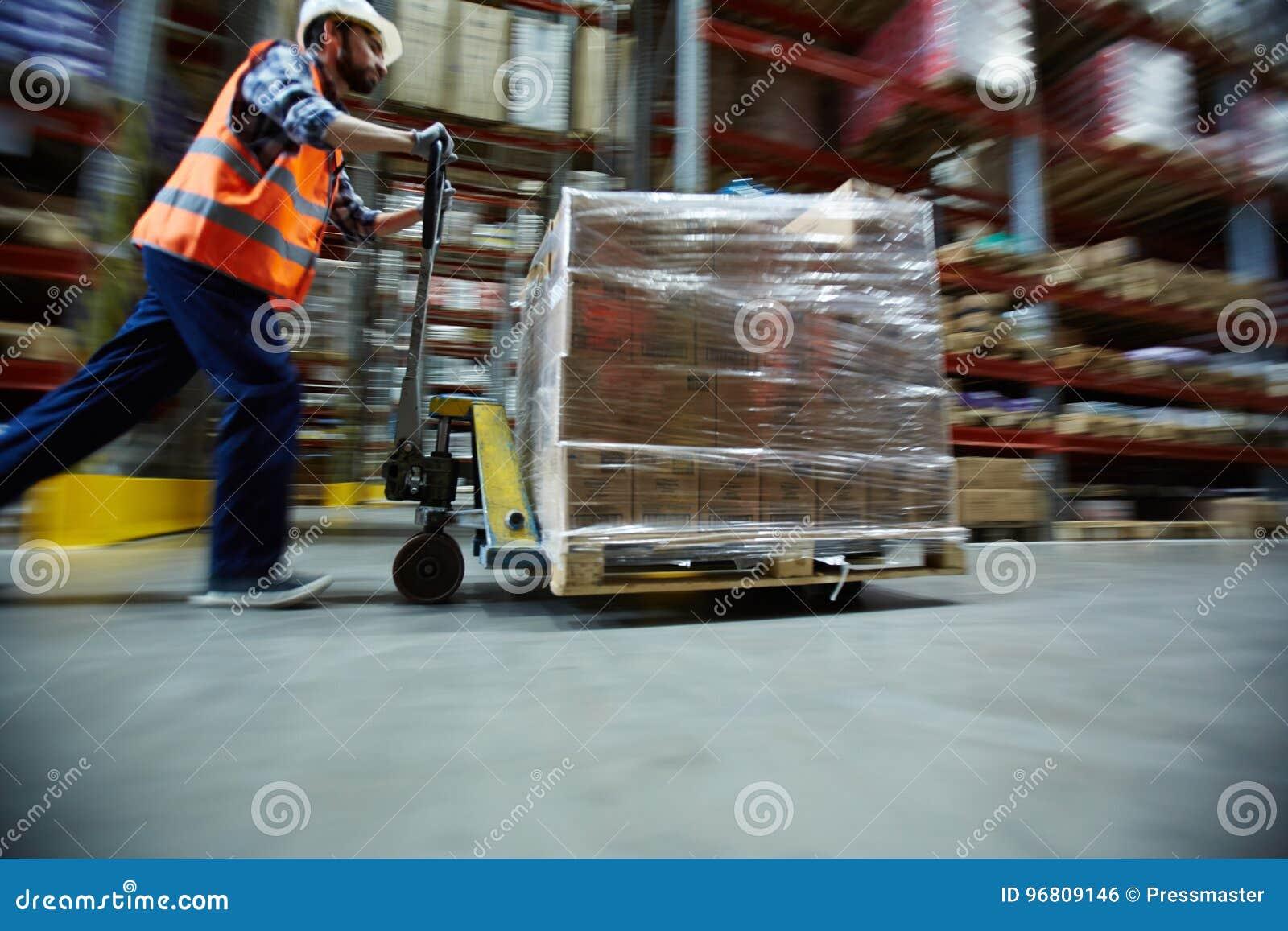 Mercanzie al minuto commoventi del lavoratore in grande magazzino