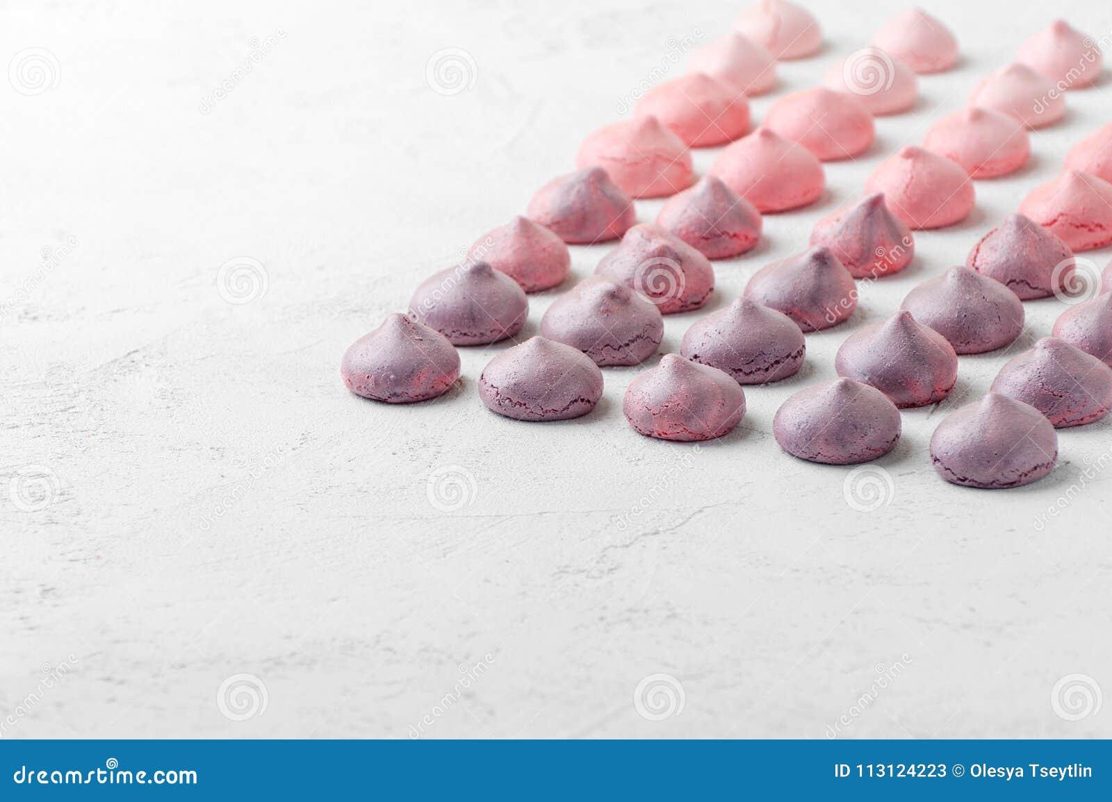 Merengues multicolores en colores púrpura-rosados en una tabla blanca