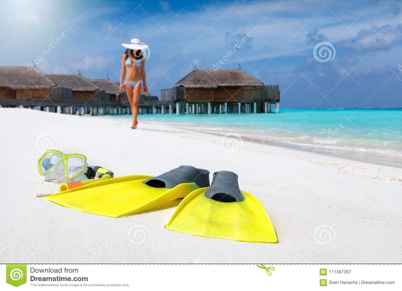 Mergulhando a engrenagem em uma praia tropical com a mulher no biquini que anda no fundo