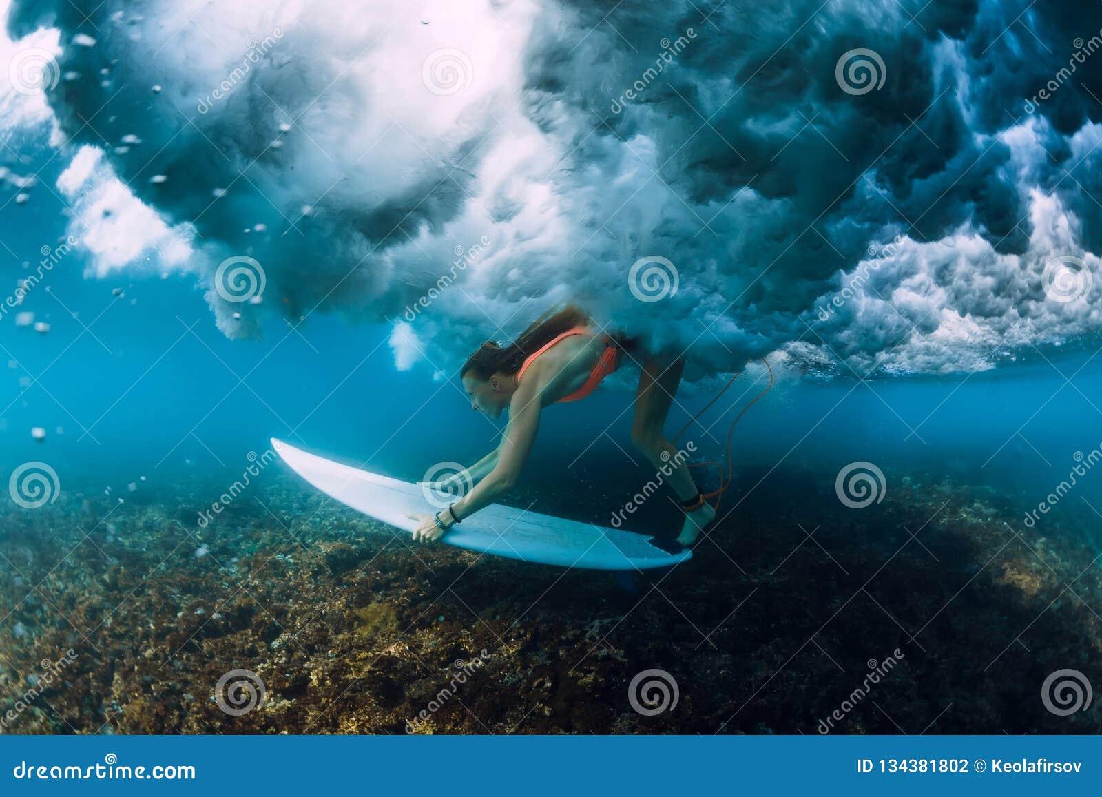 Mergulho atrativo da mulher do surfista sob a onda deixando de funcionar do tambor