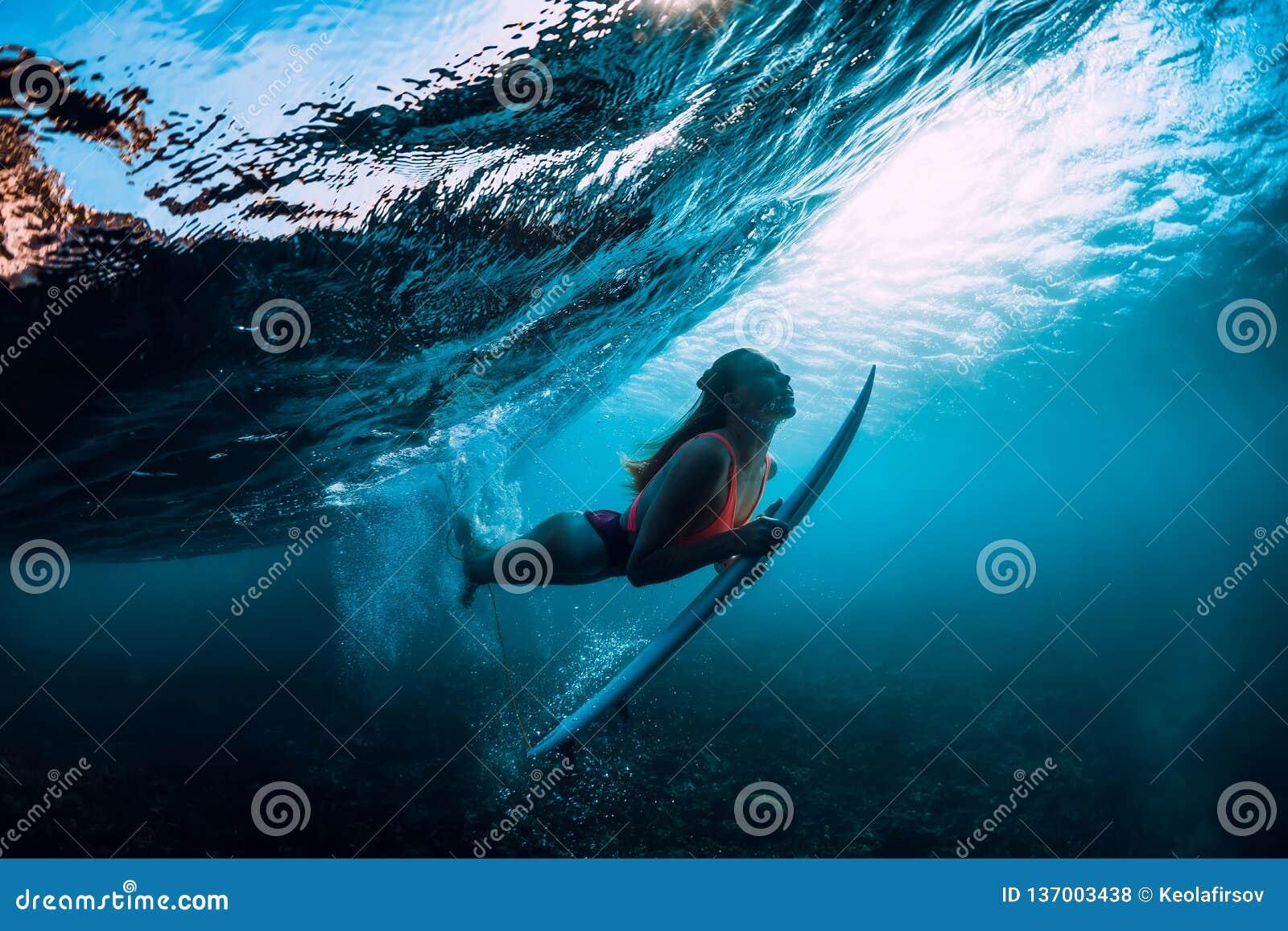 Mergulho atrativo da mulher do surfista subaquático com luz abaixo da onda e do sol