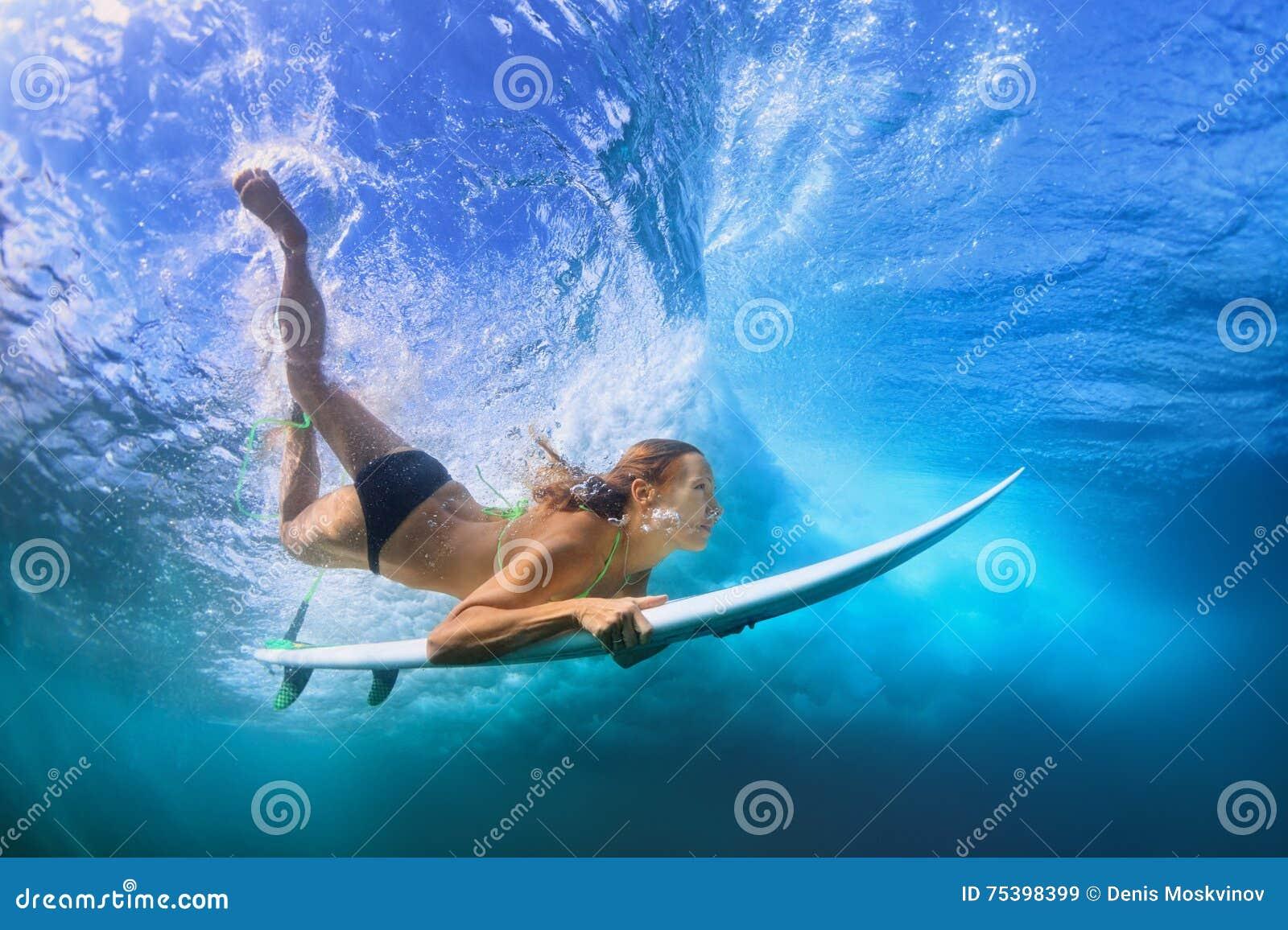 Mergulho bonito da menina do surfista sob a água com placa de ressaca