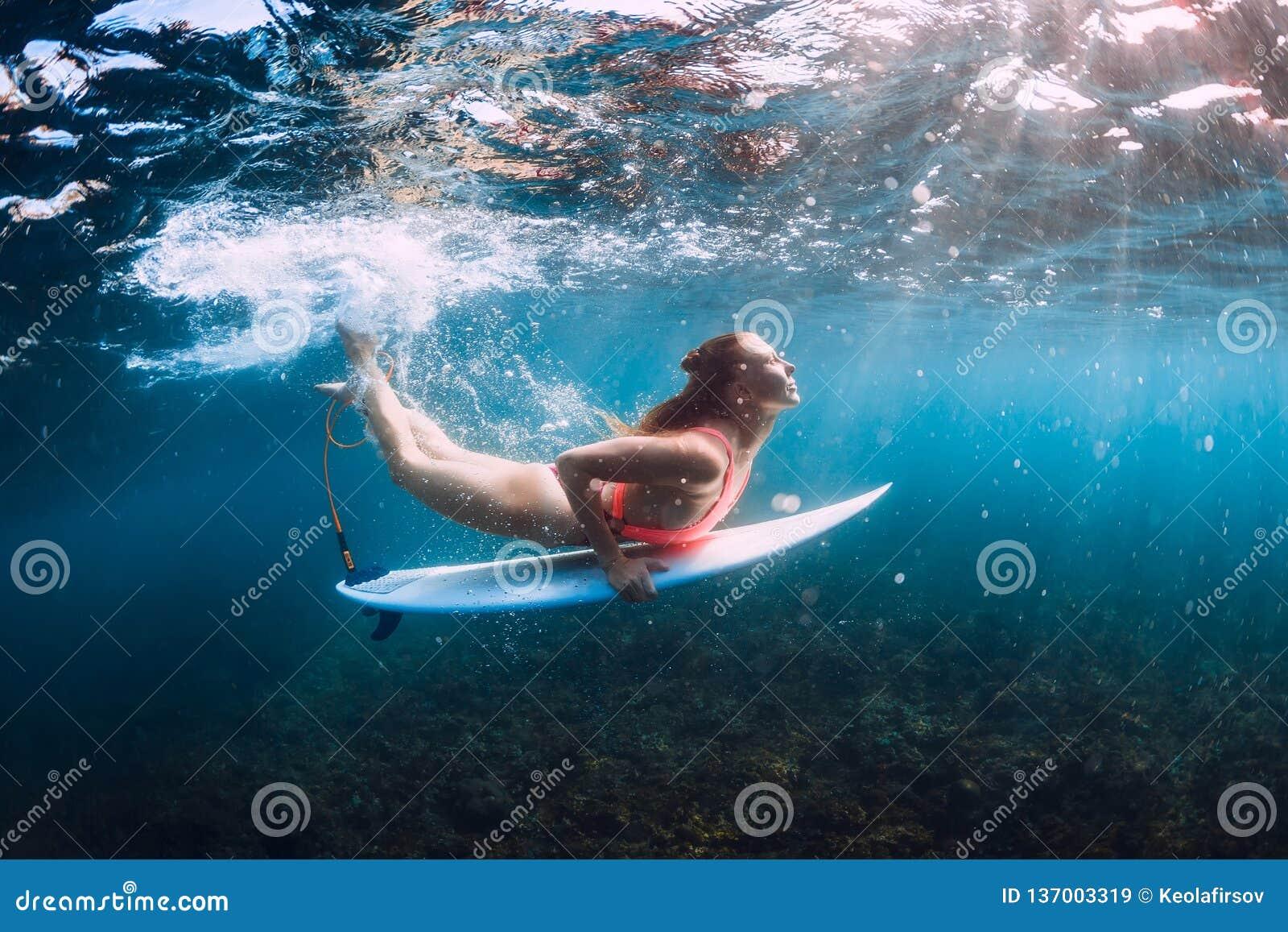 Mergulho da menina da ressaca debaixo d água com onda