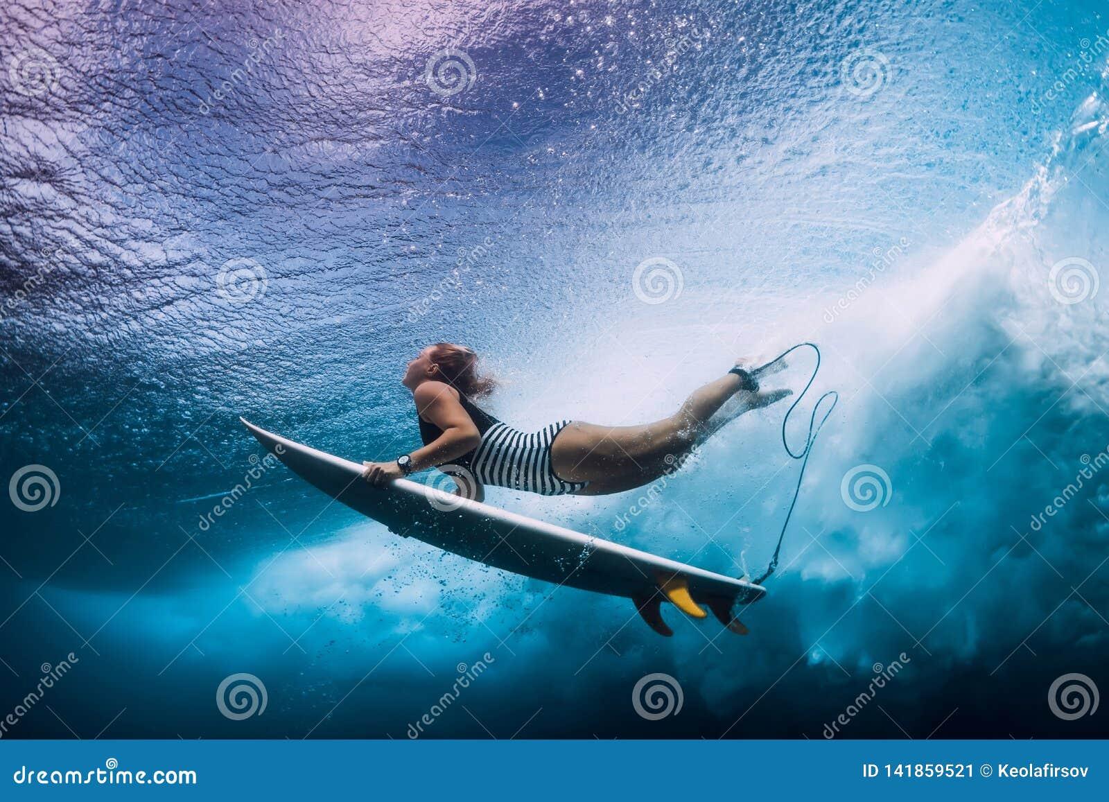 Mergulho da mulher do surfista debaixo d água Mergulho de Surfgirl sob a onda