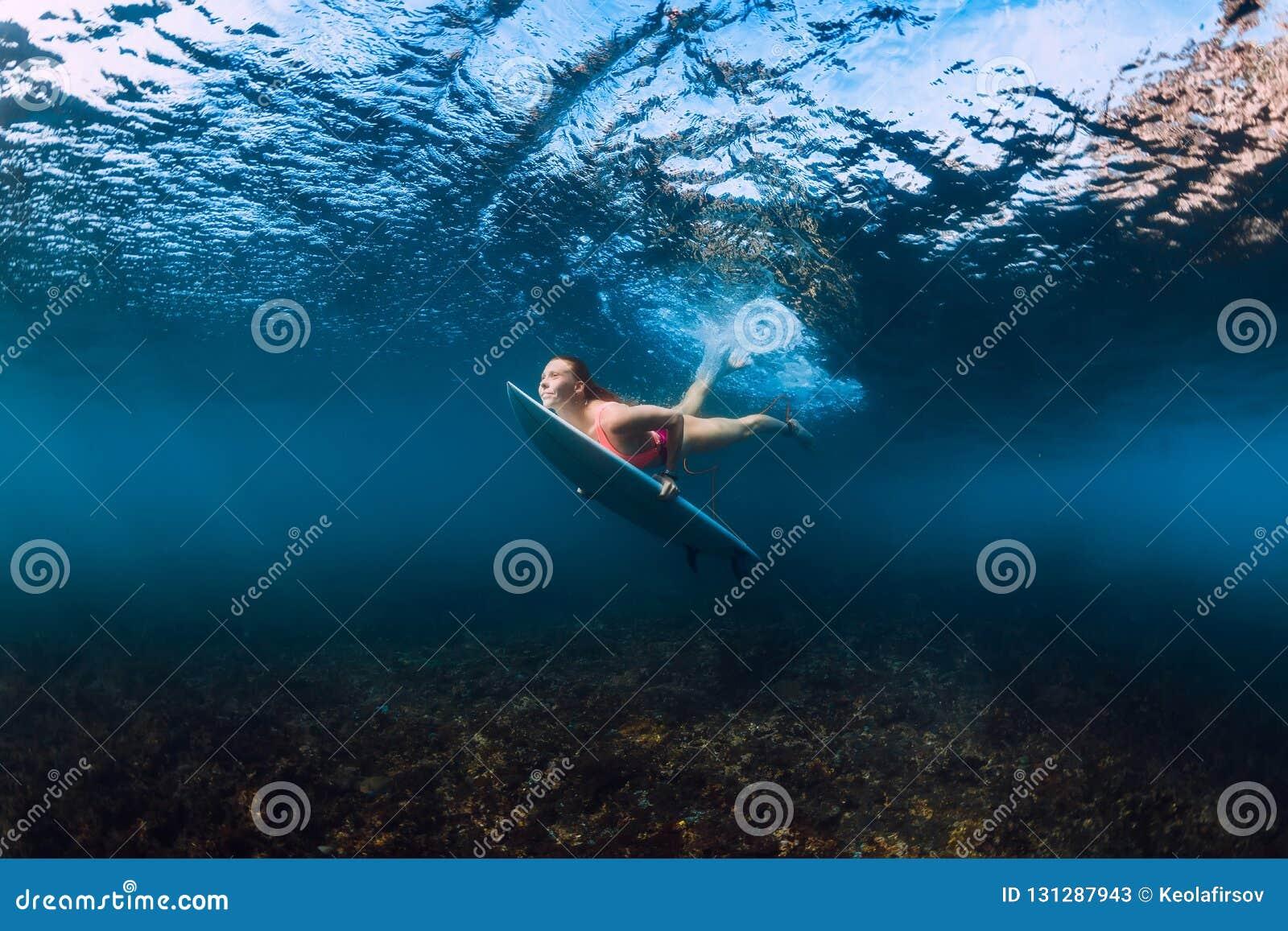 Mergulho desportivo da mulher do surfista subaquático com abaixo a onda
